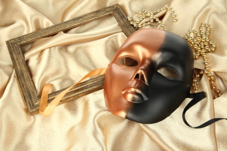 Mask on gold fabric background photo