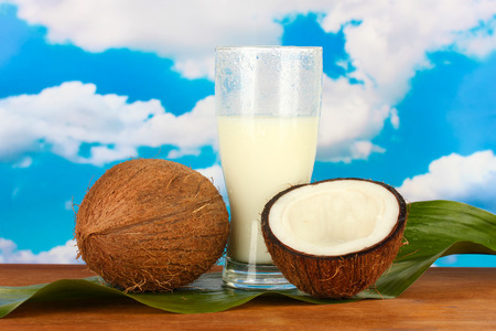 glass of coconut milk and coconuts on sky background close-up photo