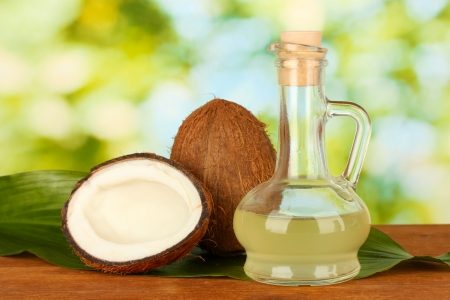 palm oil: decanter with coconut oil and coconuts on green background Stock Photo