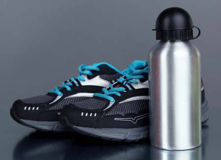 Sports bottle and sneakers on grey background photo