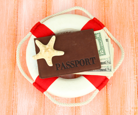 diving save: Lifebuoy  with passport and money, on color wooden background Stock Photo