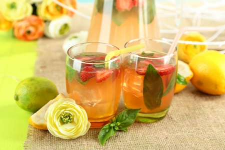 Basil lemonade with strawberry in  jug and glass, on wooden table, on bright background photo