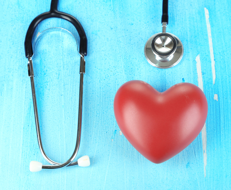 Stethoscope and heart on wooden table close-up Stock Photo - 23943133