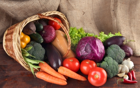 Different vegetables in basket on table on sackcloth background photo