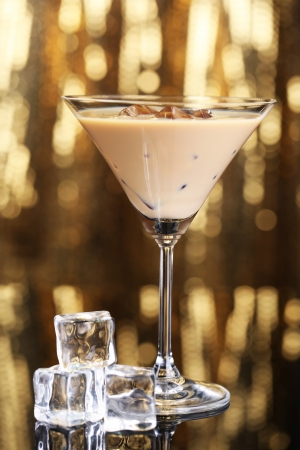 baileys: Baileys liqueur in glass on golden background Stock Photo