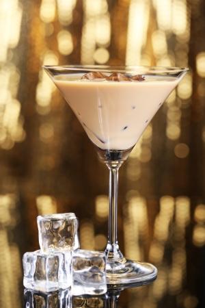 baileys: Baileys liqueur in glass on golden background Stock Photo