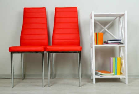 Beautiful interior with modern  color chairs,  books on wooden stand, on wall background photo