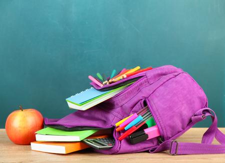 Paarse rugzak met schoolspullen op houten tafel op groene achtergrond bureau Stockfoto