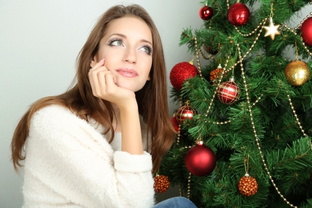 Beautiful smiling girl sitting near Christmas tree in room photo