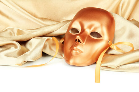 Mask on gold fabric on white background photo