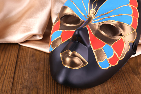 Mask on golden fabric on wooden background Stock Photo - 23943891