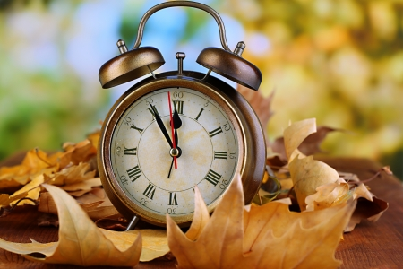 Old clock on autumn leaves on wooden table on natural background photo