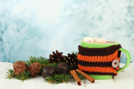 Cup of hot cacao with chocolates and fir branches on table on bright background photo