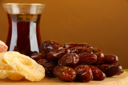 Dried dates with cup of tea and sweets on table on brown background photo