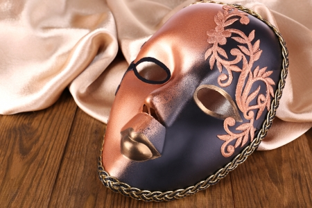 canvass: Mask on golden fabric on wooden background Stock Photo