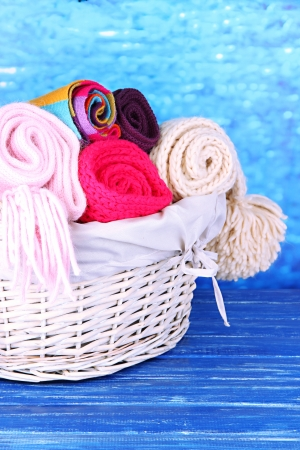 clothes interesting: Warm knitted scarves in basket on wooden table on blue background