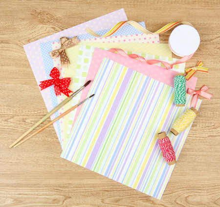 Paper for scrapbooking and tools, on wooden table photo