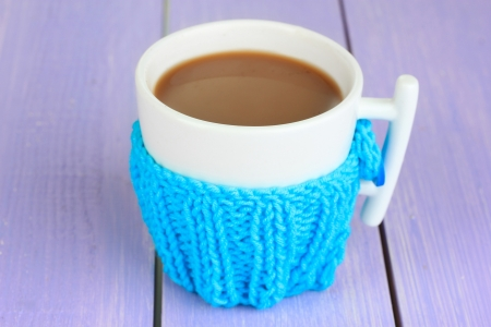 warm things: Cup with knitted thing on it on wooden table close up Stock Photo