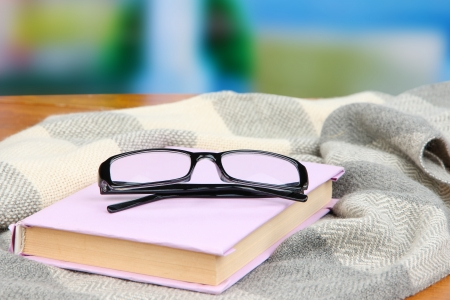 Composition with old book, eye glasses and plaid on bright background photo