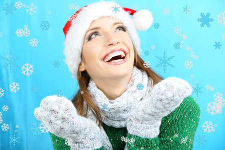 Beautiful smiling girl with snow on blue background photo