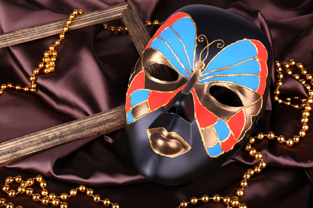 Mask on brown fabric background photo