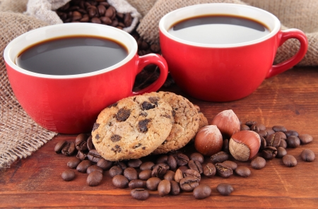 cobnut: Red cups of strong coffee with coffee beans and cookies on table on sackcloth background Stock Photo