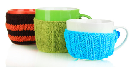 Cups with knitted things on it isolated on white photo
