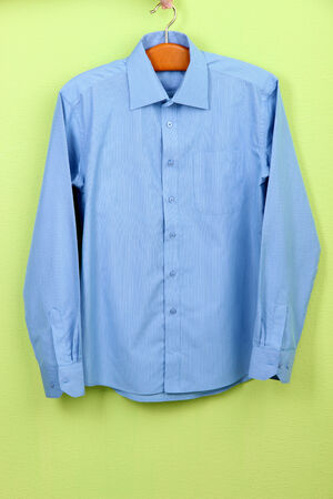 chemise: Male shirt on hanger on wall background