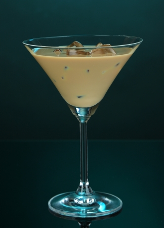 Baileys liqueur in glass on blue background photo