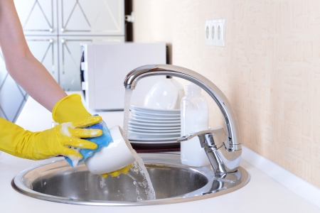 Close up hands of woman washing dishes in kitchen photo