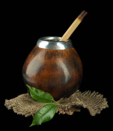 Calabash and bombilla with yerba mate isolated on black photo