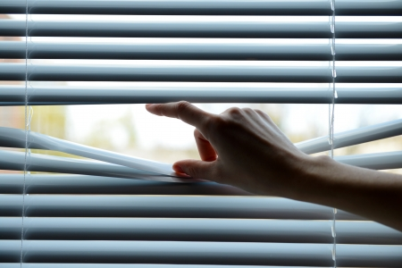 paranoia: Female hand separating slats of venetian blinds with a finger to see through Stock Photo