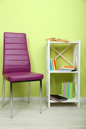 Beautiful interior with modern  color chair,  books on wooden stand, on wall background photo