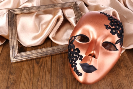 Mask on golden fabric on wooden background photo