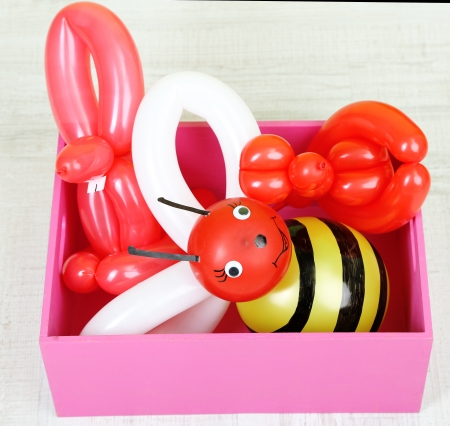 Simple balloon animals in wooden box,on gray background photo