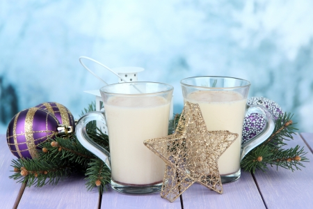 Cups of eggnog with fir branches and Christmas decorations on table on bright background Stock Photo - 24189439