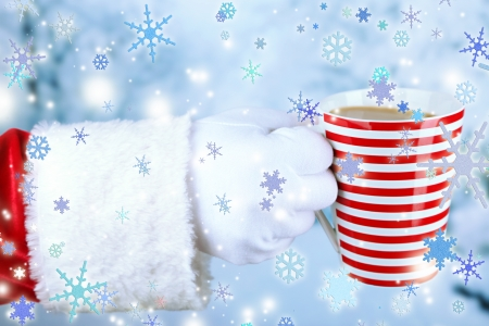 Santa holding mug in his hand, on light background photo