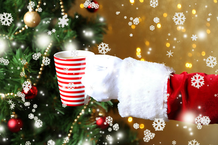 Santa holding mug in his hand, on bright background photo