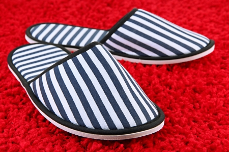 Striped slippers on carpet background photo