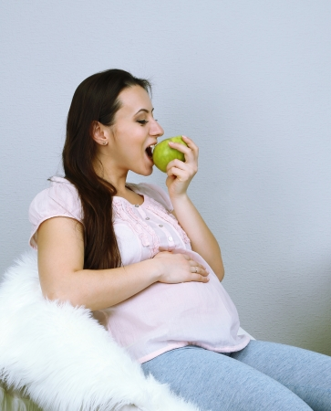 regnant: Young regnant woman sitting on armchair and eating apple on wall background