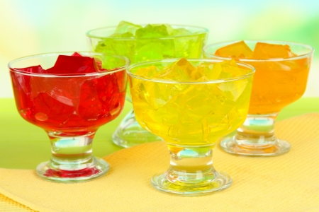 Tasty jelly cubes in bowls on table on light  Stock Photo