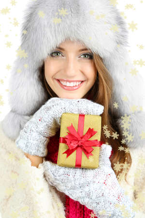 Beautiful smiling girl in hat with Christmas gift isolated on white photo