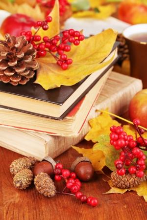 Books and autumn leaves on wooden table close-up photo
