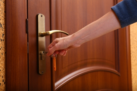 locking up: Locking up or unlocking door with key in hand