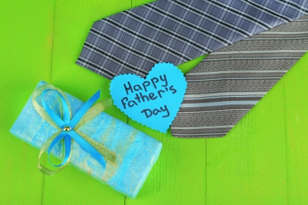 Happy Fathers Day tag with gift boxes and tie, on wooden  photo