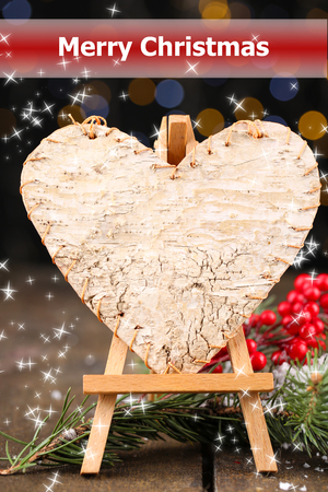 Decorative heart on easel, on wooden table, on shiny  photo