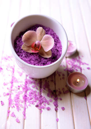Still life with beautiful blooming orchid flower, towel and bowl with sea salt, on color wooden background photo