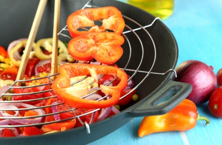 Vegetables in wok on wooden table close-up photo