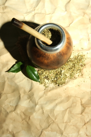 mate infusion: Calabash and bombilla with yerba mate on old paper background
