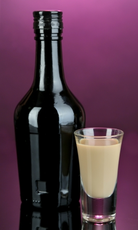 Baileys liqueur in bottle and glass on pink background photo